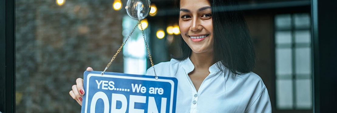 Entrepreneur hangs open for business sign