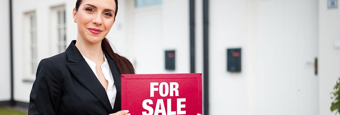 Real estate sales professional holding up sign